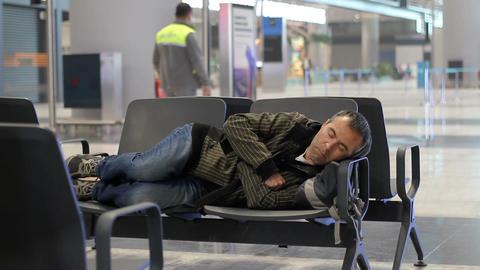 Passenger young man sleeping while waiting the plane at airport passenger terminal Footage