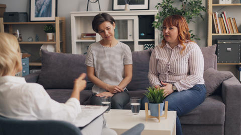 Female friends having conversation with psychotherapist talking gesturing Footage