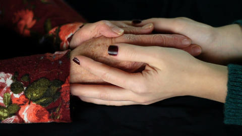Young girl caressing old woman's hands with love and compassion. Black background close up hands Footage