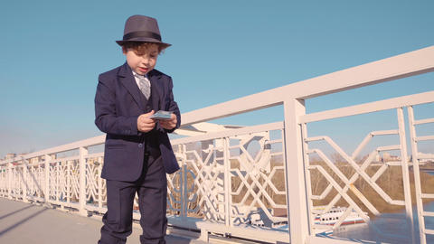 Young business boy in black suit and hat throwing money from bridge. Waste money GIF
