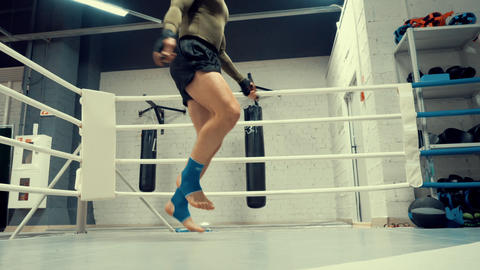 Boxer man training jump exercise on skipping rope in fight club low angle view ビデオ