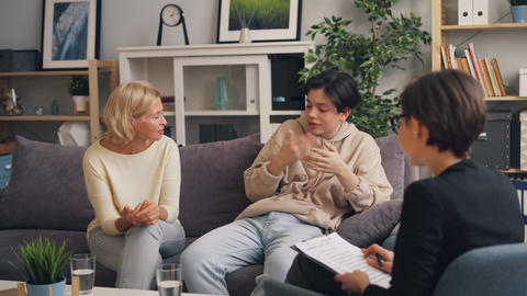 Woman and teenager discussing mother son relationship with female therapist Live Action