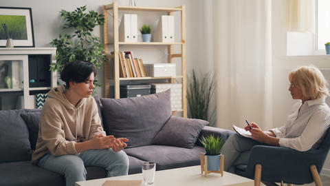 Unhappy teenager having conversation with experienced therapist in office Live Action