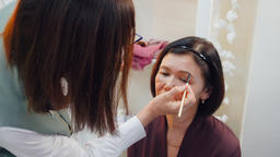 Makeup artist doing makeup eyebrows with cosmetic brush to elderly woman Footage