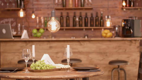 A wooden round table in an empty restaurant with cheese and grape appetizer Footage