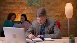 Closeup shoot of adult businessman using the laptop taking notes indoors in the Footage