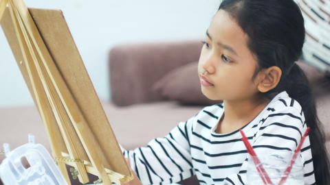 Asian little girl drawing and painting paper art for education concept Footage