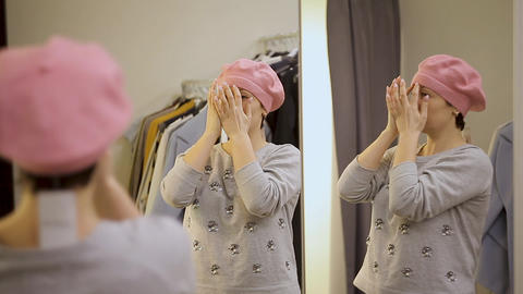 Young woman trying on clothes. Attractive caucasian woman looks in the mirror Footage