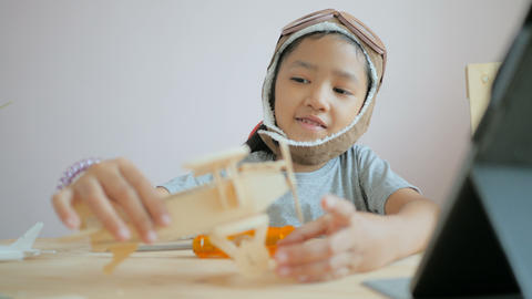 Asian little girl making air plane wooden model, Select focus shallow depth of field Footage