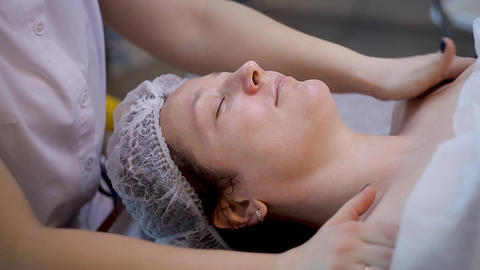 Beautiful young female relaxing female receiving facial massage, beauty spa Footage