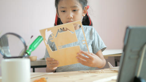 Asian little girl making air plane wooden model, Select focus shallow depth of field Live Action