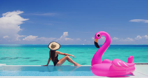 Summer Vacation Woman in bikini and inflatable pink pelican toy mattress in pool ビデオ