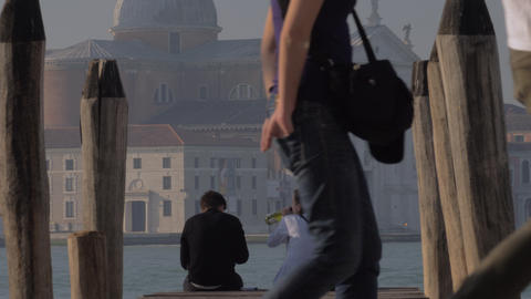 Couple sitting on the pier and drinking alcohol. Venice, Italy Archivo