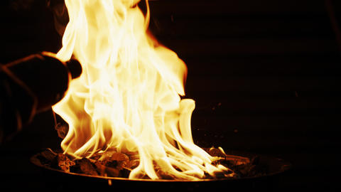 Pouring charcoal lighter fluid into barbecue grill fire. Slow motion shot on Red Footage