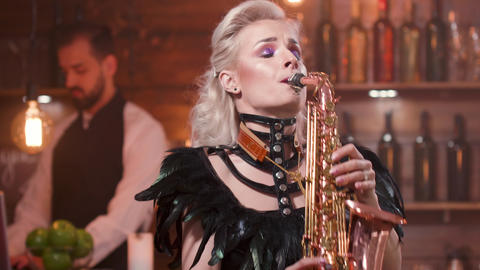 Pretty female saxophonist with bright make up performs in a restaurant Footage