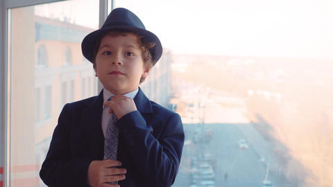 Portrait young boy in business suit, tie and hat on window background in office Live Action