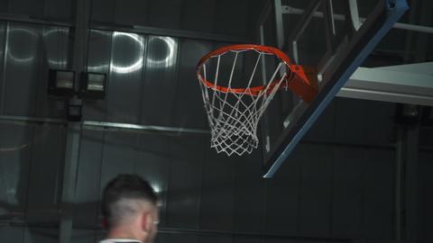Basketball player makes a slam dunk during a game. He wears unbranded sport Acción en vivo