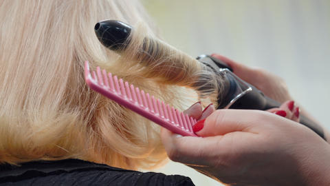 Hairstylist using hair tongs for curling blond hair of… Stock Video Footage