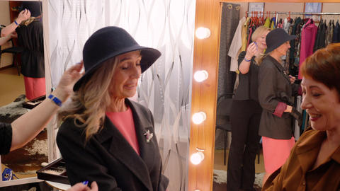 Senior fashion model trying clothes in dressing room before fashion show Live Action