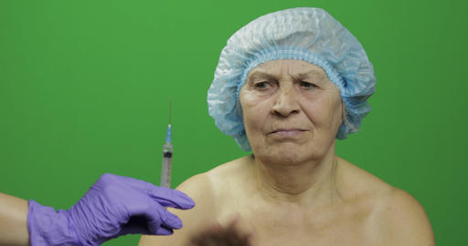 Smiling elderly female lady in protective hat scared of syringe with medicines Footage