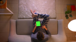Closeup top shoot of young man browsing on the tablet with green chroma screen Footage
