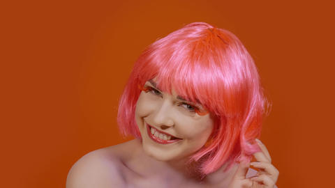 Woman blows a kiss on an orange background Footage