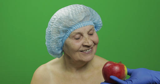 Elderly female lady in protective hat. Doctor shows her an apple Footage