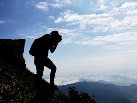 Silhouette of photographer takes photo with camera on mountain, Travel and active lifestyle concept Photo
