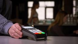 Close-up shot of woman swipes credit card through terminal machine performing Footage