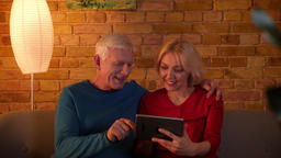 Closeup shoot of senior couple browsing web on the tablet smiling happily Footage