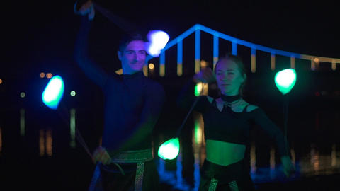 Portrait shot of two artists man and woman in black suits that spin the led poi Live Action