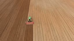 Farmer seeding, sowing crops at field.Aerial view Footage