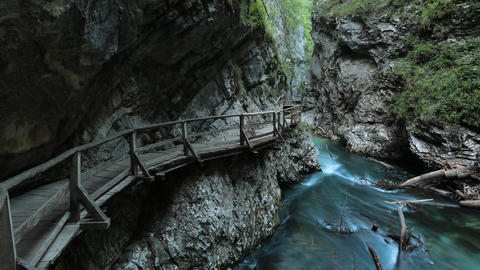 Timelapse - River going through the high walls of rock with a wood bridge stretc Footage