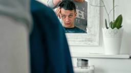 Reflection in Mirror in Barbershop of Man Explaining to Hairdresser the Haircut Archivo