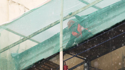Construction worker in uniform looks around standing on construction scaffolding Live Action