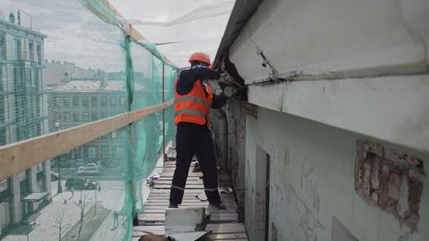 Asian male worker in orange uniform and helmet breaks…, Live Action
