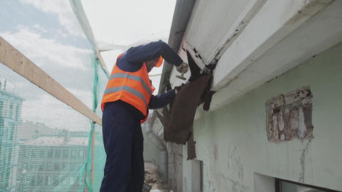 Building asian laborer in orange safety outfit breaks dirty old wooden wall Footage
