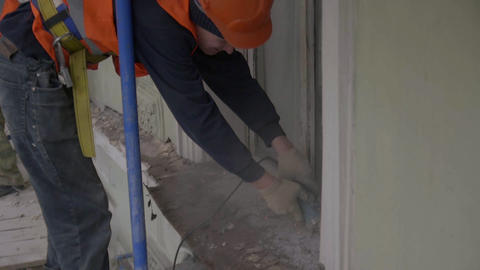 Matue guy worker uses cutting machine to cut old dust metallic part of wall Live Action