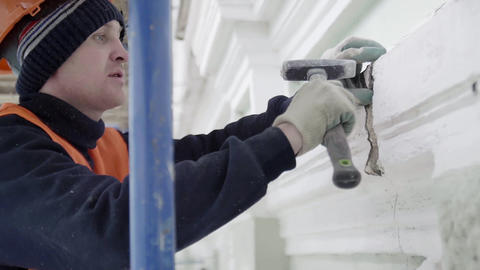 Laborer in orange unifrom polishes small part of wall with small hammer Footage