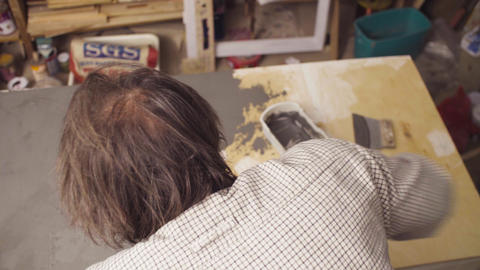 Senior man covering a wooden surface with cement Live Action