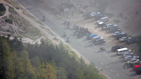 Timelapse - High angle view of a parking lot and bikers driving through mountain Live Action