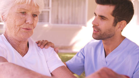 Male nurse assisting senior woman to exercise in the backyard Footage