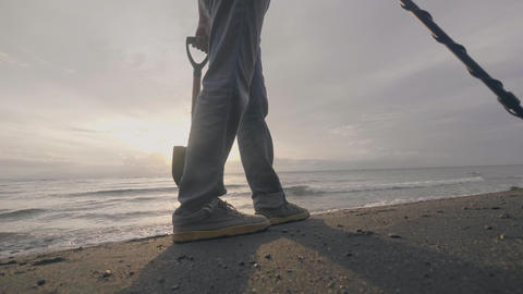 Unrecognizable man with electronic metal detector searches treasures on the Footage