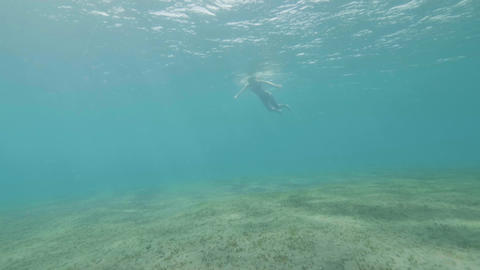 Underwater view young woman swimming and diving in blue sea water. Young woman Live Action