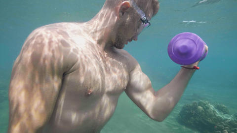 Athletic man is training with dumbbells underwater, hand exercises. Underwater Footage