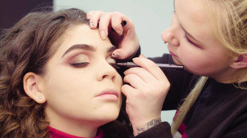 Makeup artist painting black eyeliner on the eyes Live Action