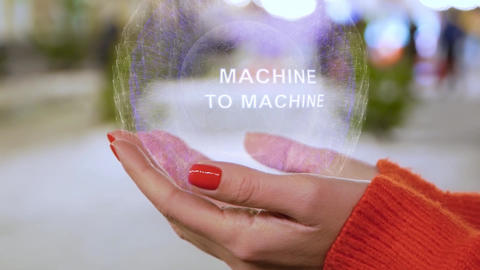 Female hands holding hologram with text Machine to machine Live Action