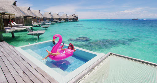 Vacation woman on inflatable Flamingo float using phone in swimming pool Footage