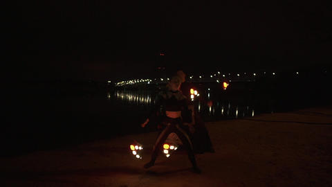 Night show of the two artsts with led poi in the shore of the river Footage
