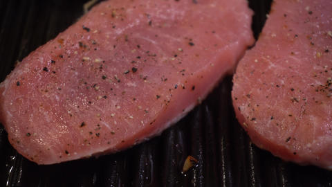 Close up of meat cooking on Cast-iron pan with heat wave and steam GIF